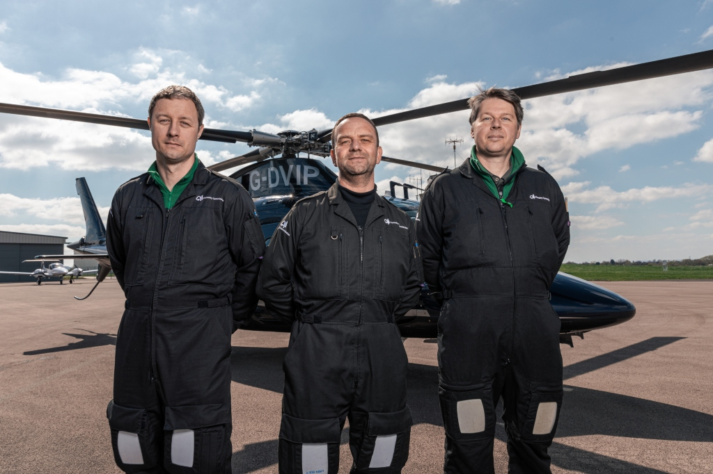 Three of the plant health team stand in a line facing the camera in front of a helicopter